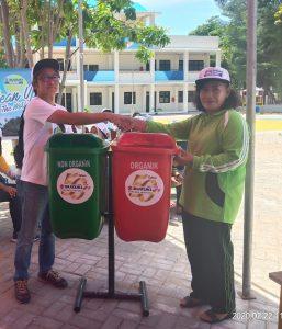 Kepala Departemen Suzuki Marine Kensuke Ikeda menyerahkan bantuan tempat sampah kepada Kepala Sekolah SDN 01 Pulau Pari Puji Rahayu. Foto: Wisesa/TROPIS.CO