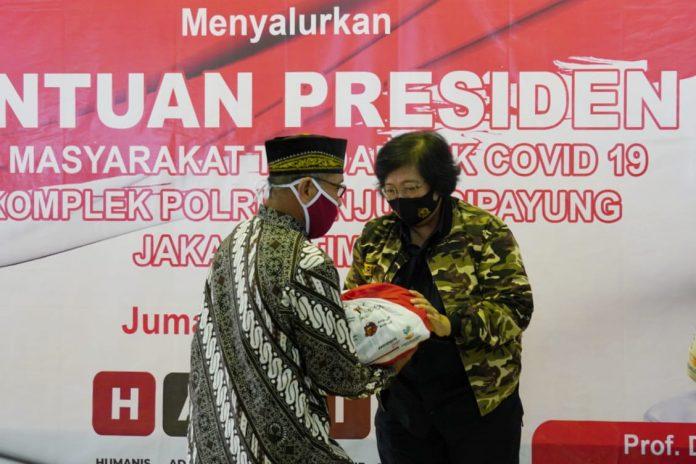 Menteri Lingkungan Hidup dan Kehutanan Siti Nurbaya menyerahkan bantuan presiden Joko Widodo, berupa paket sembako di keluarga besar purnawirawan TNI-Polri di Mujul, Cipayung. Foto: Istimewa