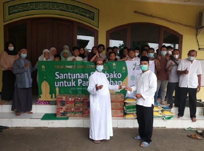 Ketua Forum Jurnalis Sawit (FJS) Sudarsono secara simbolis menyerahkan bantuan kepada pengurus Panti Asuhan Al Mukhlisin, Ciracas Jakarta Timur. Foto: FJS