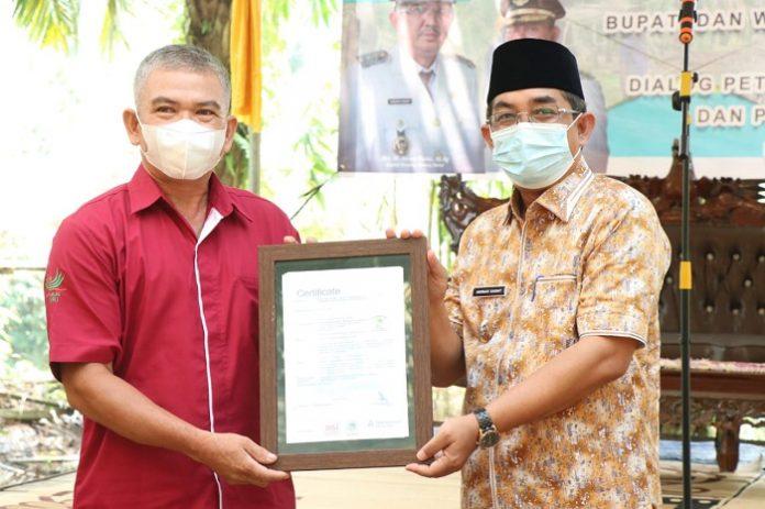 Drs. KH. Anwar Sadat (kanan), M.Ag, Bupati Tanjung Jabung Barat, menyerahkan sertifikat RSPO (Roundtable on Sustainable Palm Oil) kepada perwakilan Forum Petani Swadaya Merlung Renah Mendaluh (FPS-MRM). Foto: berkabar.id